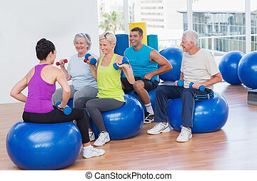 People lifting dumbbells in gym class - Female instructor...