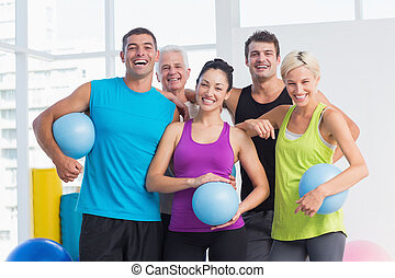 Cheerful people with medicine balls in fitness studio -...