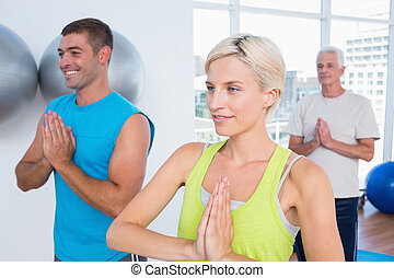People meditating in fitness club