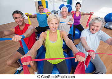 Happy people exercising with resistance bands in gym class -...