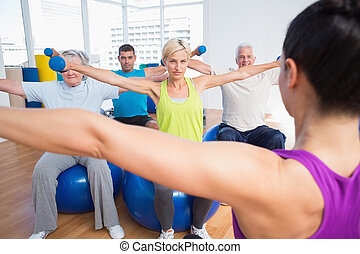 People working out with dumbbells in fitness club