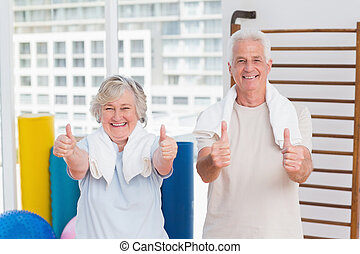 Senior couple gesturing thumbs up in gym - Portrait of happy...