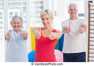 Instructor with senior couple showing thumbs up in gym -...