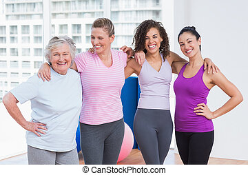 Female friends standing arms around in fitness studio -...