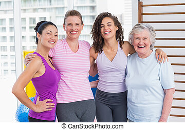 Happy women standing arms around in gym - Portrait of happy...