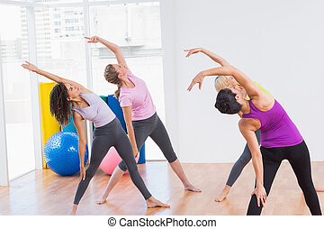 Trainer and female friends doing stretching exercise