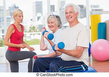 happy senior couple lifting dumbbells while instructor...