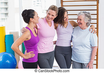 Female friends standing arms around in gym - Happy female...