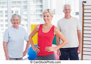 Confident female instructor with senior couple