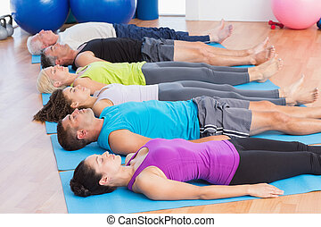 People meditating on exercise mats in fitness club - Fit men...