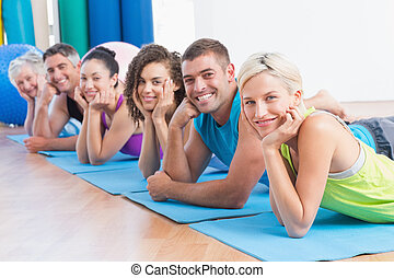 People relaxing on exercise mats at fitness studio -...