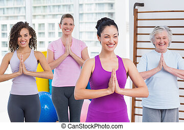 Friends with hands clasped standing in gym - Happy female...