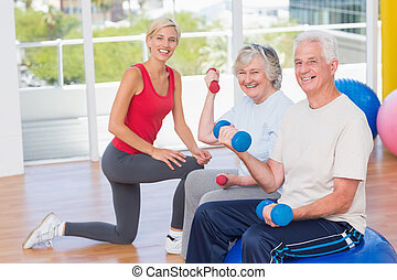 Happy senior couple lifting dumbbells by trainer - Portrait...