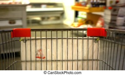 Customer shopping at supermarket with trolley and blurred background. Video shift motion time lapse speed up