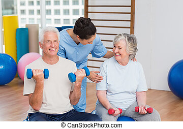 Female instructor with senior couple in gym - Happy female...