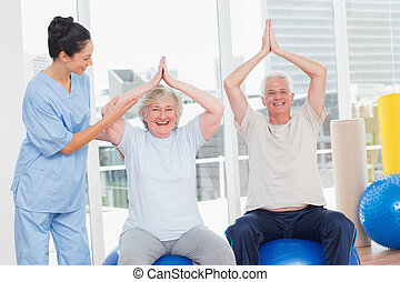 Senior couple on exercis ball being assisted by trainer -...