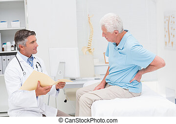 Doctor discussing reports with patient suffering from back...