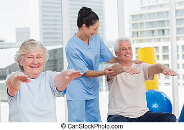 Trainer assisting senior couple in exercising - Happy young...