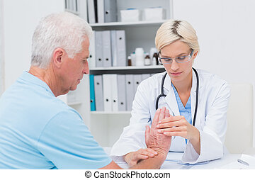 Female physiotherapist examining male patients wrist