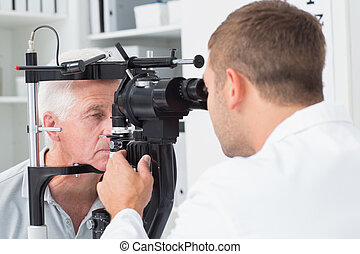 Optician examining senior patients eyes through slit lamp -...
