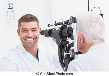 Happy optometrist examining senior patients eye - Portrait...