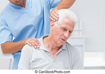 Physiotherapist giving physical therapy to senior patient -...