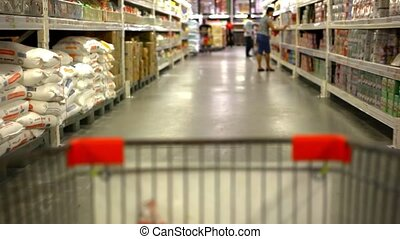 Customer shopping at supermarket with trolley. Video shift motion