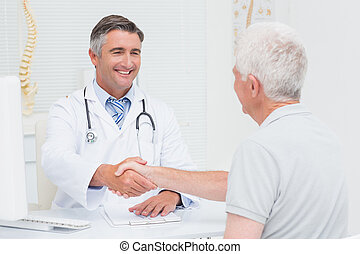 Doctor shaking hands with senior patient - Happy male doctor...