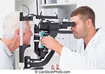 Optometrist examining senior patients eyes through slit lamp...