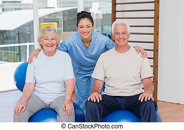 Female trainer with arms around senior couple - Portrait of...