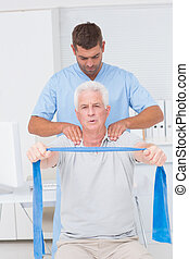Physiotherapist assisting senior man in exercising with resistan