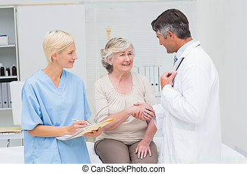 Doctor and patient shaking hands while nurse writing reports...