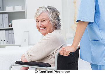 Senior patient in wheelchair being pushed by nurse