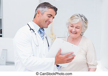 Doctor and patient discussing over reports - Happy doctor...