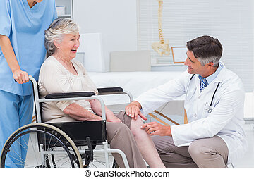 Doctor examining senior womans knee