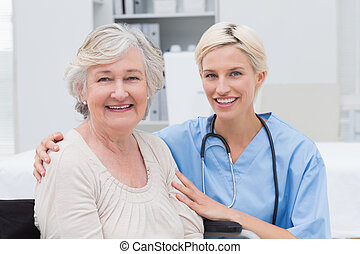 Nurse with arm around senior patient in clinic - Portrait of...