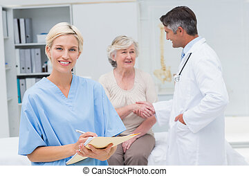 Nurse making reports while doctor and patient shaking hands...