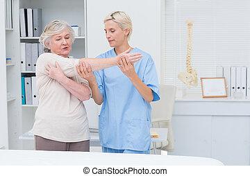 Nurse assisting senior patient in raising arm - Nurse...