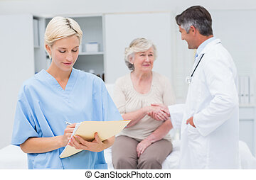 Female nurse making reports while doctor and patient shaking...