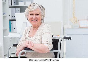 Happy senior woman sitting on wheelchair - Portrait of happy...