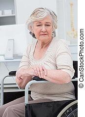 Sad senior patient sitting in wheelchair
