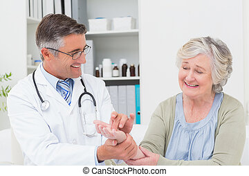 Male doctor examining patients hand at table - Happy male...
