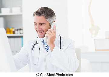 Male doctor using landline phone - Happy male doctor using...