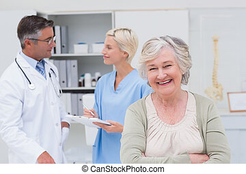 Patient smiling while doctor and nurse discussing in background
