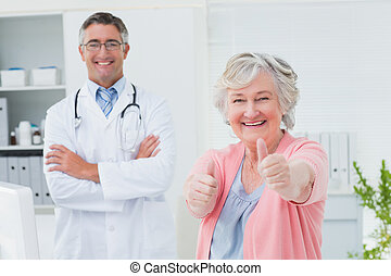 Patient showing thumbs up sign while standing with doctor -...