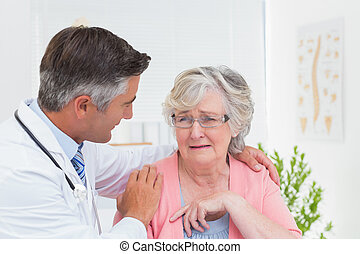 Doctor consoling senior patient in clinic - Male doctor...