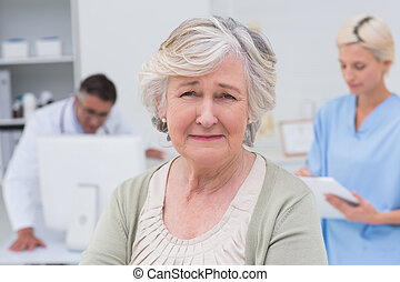 Unhappy patient with doctor and nurse working in background...