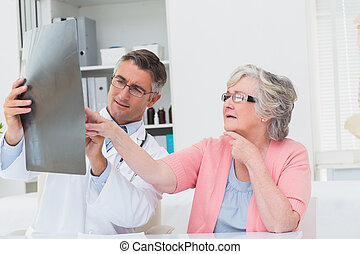 Doctor explaining x-ray to senior patient - Male doctor...