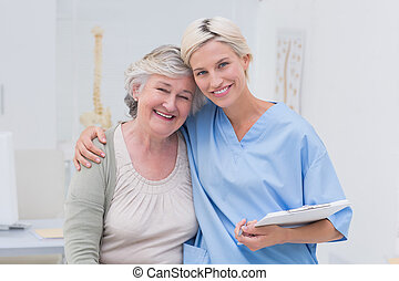 Friendly nurse with arm around seni - Portrait of friendly...