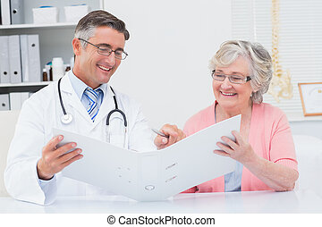 Doctor and female patient looking at reports in file - Happy...